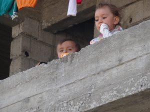 two Yazidi kids peeking over concrete